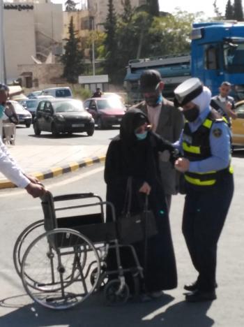 شرطية تقدم مساعدة لمسنة امام قصر العدل (صور)
